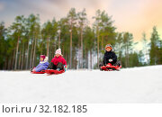 kids sliding on sleds down snow hill in winter. Стоковое фото, фотограф Syda Productions / Фотобанк Лори