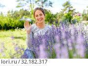 young woman and lavender flowers at summer garden. Стоковое фото, фотограф Syda Productions / Фотобанк Лори