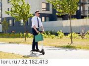 Купить «businessman with shopping bag riding scooter», фото № 32182413, снято 1 августа 2019 г. (c) Syda Productions / Фотобанк Лори