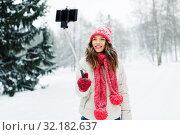 Купить «young woman taking selfie by monopod in winter», фото № 32182637, снято 29 января 2019 г. (c) Syda Productions / Фотобанк Лори