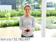 Купить «young woman with handful of soil at summer garden», фото № 32182697, снято 12 июля 2019 г. (c) Syda Productions / Фотобанк Лори