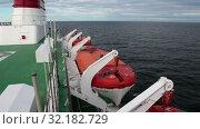 Купить «Оранжевые спасательные шлюпки висят по бокам судна. Круизный лайнер Viking Line в Балтийском море», видеоролик № 32182729, снято 17 июня 2019 г. (c) Кекяляйнен Андрей / Фотобанк Лори