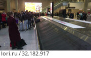 Bags and suits come on baggage conveyor belt in baggage delivery area. Arrival lounge of the Pulkovo International airport. Passengers find their things (2019 год). Редакционное видео, видеограф Кекяляйнен Андрей / Фотобанк Лори