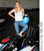 Купить «Smiling woman with helmet standing near cars for motor racing in sport club», фото № 32185105, снято 22 октября 2019 г. (c) Яков Филимонов / Фотобанк Лори