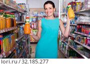 Купить «Smiling girl is holding bottle with juice», фото № 32185277, снято 6 июня 2017 г. (c) Яков Филимонов / Фотобанк Лори