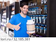 Купить «sportsman holding thumb up and sport nutrition», фото № 32185381, снято 28 марта 2018 г. (c) Яков Филимонов / Фотобанк Лори