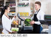 Купить «Seller assisting customer to weigh purchases», фото № 32185481, снято 23 ноября 2016 г. (c) Яков Филимонов / Фотобанк Лори