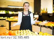 Купить «Female seller showing assortment», фото № 32185485, снято 23 ноября 2016 г. (c) Яков Филимонов / Фотобанк Лори