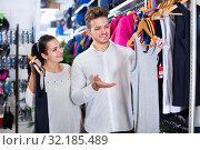 Купить «Couple choosing new sportswear in sports store», фото № 32185489, снято 22 ноября 2016 г. (c) Яков Филимонов / Фотобанк Лори