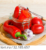 Homemade summer crop preservation, vegetable vegetarian diet wholesome food, natural red roasted bell peppers with garlic marinated in a glass jar on a table. Стоковое фото, фотограф Светлана Евграфова / Фотобанк Лори