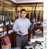 Купить «Salesman showing rifle», фото № 32188373, снято 11 декабря 2017 г. (c) Яков Филимонов / Фотобанк Лори