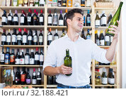 Man expert holding wine bottles in winery section. Стоковое фото, фотограф Яков Филимонов / Фотобанк Лори