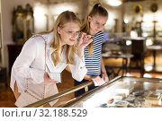 Купить «Woman visitor with daughter looking to art objects under glass with guide book», фото № 32188529, снято 21 октября 2018 г. (c) Яков Филимонов / Фотобанк Лори