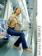 Купить «Smiling young woman passenger standing inside train at metro», фото № 32188613, снято 31 марта 2019 г. (c) Яков Филимонов / Фотобанк Лори