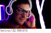 Купить «man in headphones over neon lights of night club», видеоролик № 32189013, снято 15 октября 2019 г. (c) Syda Productions / Фотобанк Лори