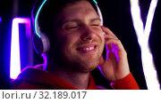 Купить «man in headphones over neon lights of night club», видеоролик № 32189017, снято 15 октября 2019 г. (c) Syda Productions / Фотобанк Лори