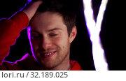Купить «portrait of man in dark room over neon lights», видеоролик № 32189025, снято 15 октября 2019 г. (c) Syda Productions / Фотобанк Лори