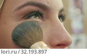 Applying blush makeup with brush to cheekbones of young woman. Стоковое видео, видеограф Vasily Alexandrovich Gronskiy / Фотобанк Лори