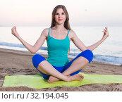 Купить «Female 20-25 years old is sitting and practicing meditation in blue T-shirt», фото № 32194045, снято 4 августа 2017 г. (c) Яков Филимонов / Фотобанк Лори