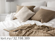 Купить «bed with pillows, blanket and open book at home», фото № 32198389, снято 15 октября 2016 г. (c) Syda Productions / Фотобанк Лори