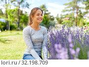 Купить «young woman and lavender flowers at summer garden», фото № 32198709, снято 12 июля 2019 г. (c) Syda Productions / Фотобанк Лори