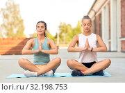 Купить «women doing yoga and meditating in lotus pose», фото № 32198753, снято 28 июля 2019 г. (c) Syda Productions / Фотобанк Лори