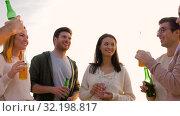 friends with non alcoholic drinks talking on beach. Стоковое видео, видеограф Syda Productions / Фотобанк Лори