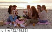 Купить «happy friends eating sandwiches at picnic on beach», видеоролик № 32198881, снято 9 сентября 2019 г. (c) Syda Productions / Фотобанк Лори