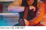 Купить «A muscular man applying elastic bandage on his wrist sitting in the gym in neon lighting», видеоролик № 32198997, снято 21 сентября 2019 г. (c) Константин Шишкин / Фотобанк Лори