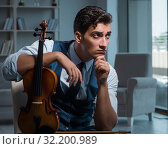Купить «Young musician man practicing playing violin at home», фото № 32200989, снято 15 августа 2017 г. (c) Elnur / Фотобанк Лори