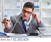 Купить «Businessman in the office smoking holding human skull», фото № 32202829, снято 25 апреля 2017 г. (c) Elnur / Фотобанк Лори