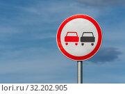 Купить «Запрещающий дорожный знак «Обгон запрещен» запрещает обгон всех транспортных средств на автодороге. Вид на знак на фоне синего неба и облаков в солнечную погоду», фото № 32202905, снято 11 августа 2019 г. (c) А. А. Пирагис / Фотобанк Лори