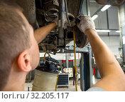 Автомеханик подключает прибор для замены тормозной жидкости к штуцеру барабана (2019 год). Редакционное фото, фотограф Вячеслав Палес / Фотобанк Лори