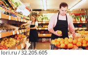 Купить «Young man in apron selling fresh oranges and fruits on the supermarket», видеоролик № 32205605, снято 26 мая 2019 г. (c) Яков Филимонов / Фотобанк Лори