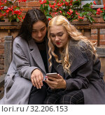 Купить «Two girlfriends discussing something while looking into a smartphone», фото № 32206153, снято 19 сентября 2019 г. (c) Евгений Харитонов / Фотобанк Лори