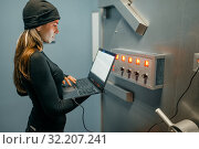 Купить «Female robber with laptop trying to open the vault», фото № 32207241, снято 3 июня 2019 г. (c) Tryapitsyn Sergiy / Фотобанк Лори