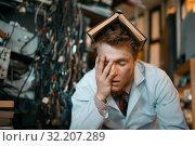 Купить «Tired strange engineer with book on his head», фото № 32207289, снято 17 июня 2019 г. (c) Tryapitsyn Sergiy / Фотобанк Лори