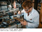 Купить «Strange scientist soldering chips, test in lab», фото № 32207297, снято 17 июня 2019 г. (c) Tryapitsyn Sergiy / Фотобанк Лори