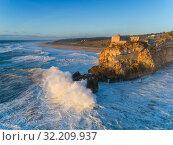 Купить «Lighthouse and big waves at in Nazare», фото № 32209937, снято 19 февраля 2019 г. (c) Михаил Коханчиков / Фотобанк Лори