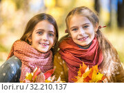 Two cute smiling 8 years old girls posing together in a park on a sunny autumn day. Стоковое фото, фотограф Sergey Borisov / Фотобанк Лори
