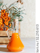Vegetarian food, healthy nutrition, preserving the harvest of homemade ripe juicy sea-buckthorn, preparing fresh healthy vitamin drink and healing broth. Bottle of juice and branches of orange sea buckthorn. Стоковое фото, фотограф Светлана Евграфова / Фотобанк Лори