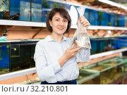 Купить «Woman holding plastic bag with fish», фото № 32210801, снято 27 февраля 2019 г. (c) Яков Филимонов / Фотобанк Лори