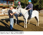 Купить «Woman and man with trainer riding horse at farm at summer day», фото № 32210881, снято 4 июля 2018 г. (c) Яков Филимонов / Фотобанк Лори