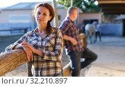 Mature smiling couple holding a surcingle and standing at farm. Стоковое фото, фотограф Яков Филимонов / Фотобанк Лори
