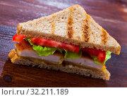 Купить «Tasty sandwich with fried chicken nuggets, tomatoes and lettuce», фото № 32211189, снято 12 декабря 2019 г. (c) Яков Филимонов / Фотобанк Лори