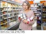 Купить «Ordinary woman choosing fresh dairy products», фото № 32216145, снято 8 февраля 2019 г. (c) Яков Филимонов / Фотобанк Лори