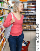 Купить «Mature woman carrying full shopping basket», фото № 32216165, снято 8 февраля 2019 г. (c) Яков Филимонов / Фотобанк Лори