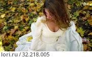 Купить «Autumn girl in lyrics style with fall leaves outdoor», видеоролик № 32218005, снято 23 сентября 2019 г. (c) Gennadiy Poznyakov / Фотобанк Лори