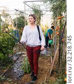 Купить «Woman gardener working with spraying apparatus in greenhouse, boy on background», фото № 32218745, снято 13 августа 2018 г. (c) Яков Филимонов / Фотобанк Лори