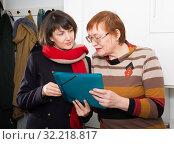 Girl volunteer offers an older woman to read the document. Стоковое фото, фотограф Яков Филимонов / Фотобанк Лори